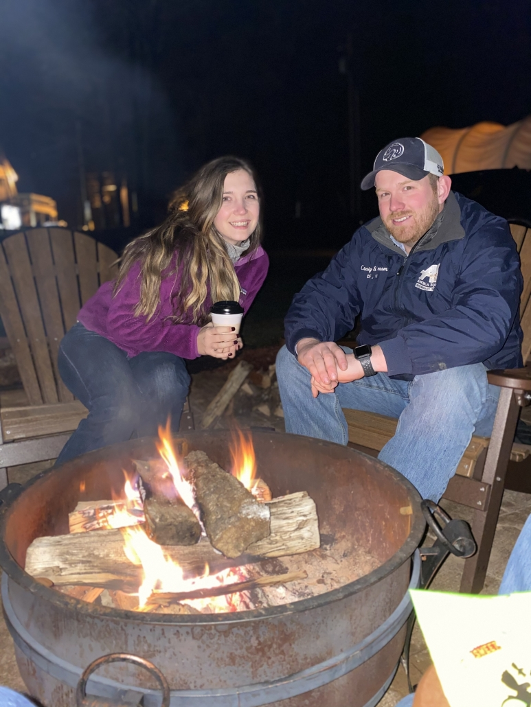 Woman and man sitting by a fire at Horse Cave KOA in Horse Cave, Kentucky.