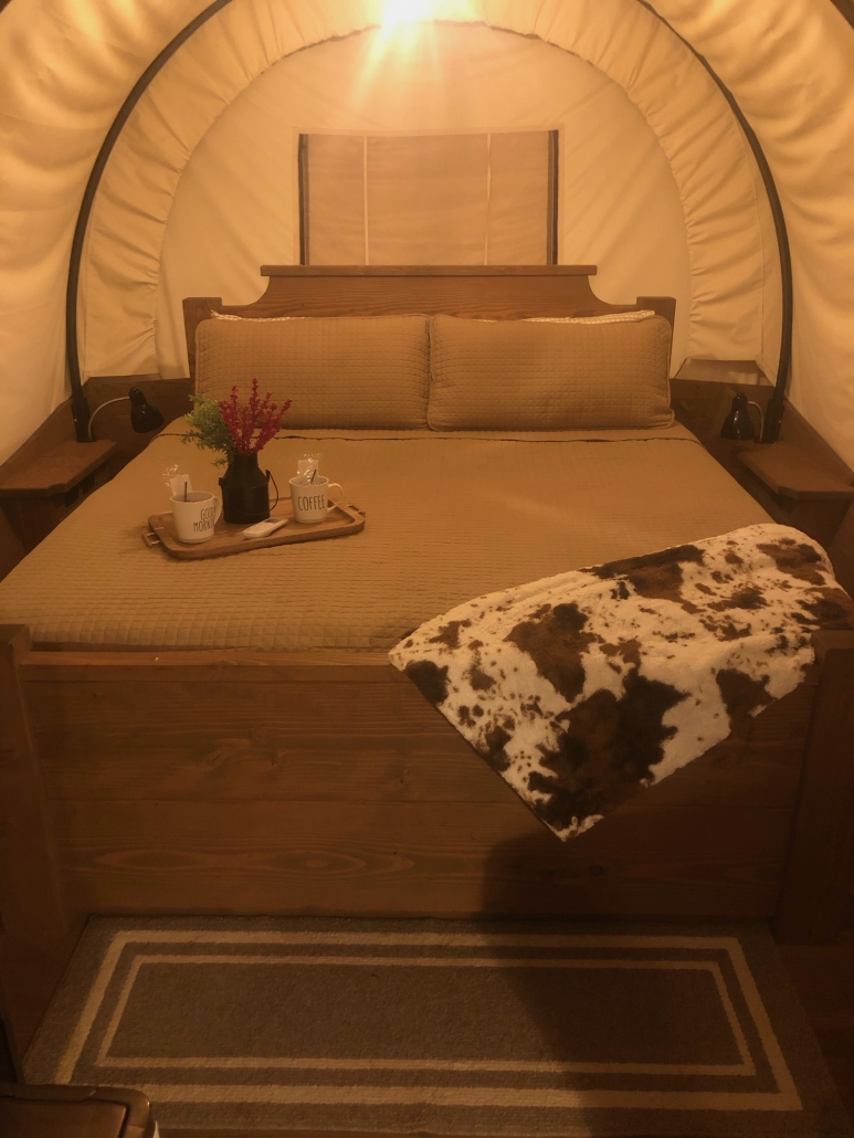 King bed with blanket and breakfast tray at Horse Cave KOA, Conestoga wagon Camping at its best.